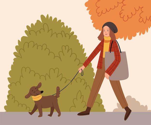 Stylowa dziewczyna wyprowadza szczęśliwego psa w szaliku w jesiennym parkujesienny nastrójspacer na świeżym powietrzu