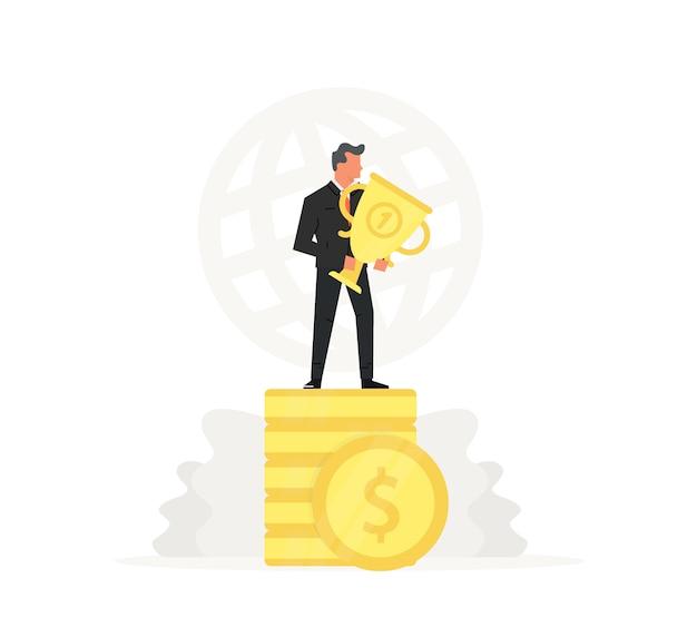 Sukces i młody biznesmen stoją na monety i trzyma złote trofeum.