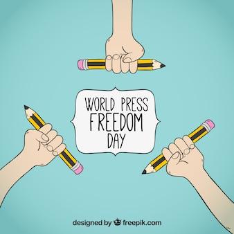 Świat wolności prasa dzień tła z rąk gospodarstwa ołówki