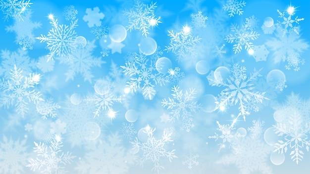Świąteczna ilustracja z białymi niewyraźnymi płatkami śniegu, blaskiem i iskierkami na jasnoniebieskim tle