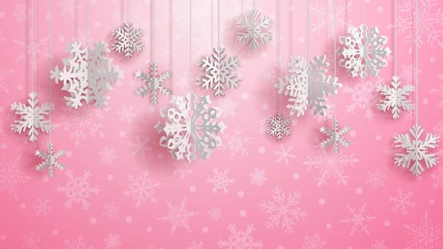 Świąteczna ilustracja z białymi trójwymiarowymi papierowymi płatkami śniegu wiszącymi na różowym tle