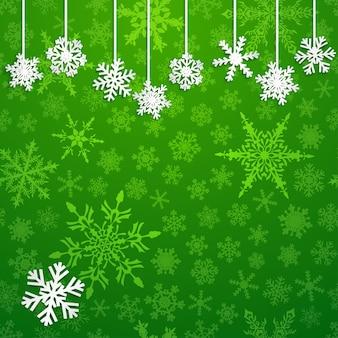 Świąteczna ilustracja z białymi wiszącymi płatkami śniegu na zielonym tle
