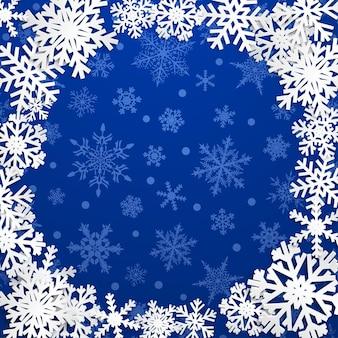 Świąteczna ilustracja z okrągłą ramą białych płatków śniegu na niebieskim tle