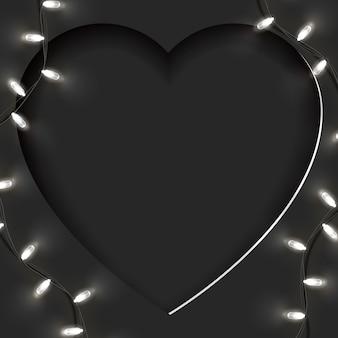 Świąteczna kartka w kształcie dużego papieru wyciętego w serce i jasnej girlandy z pustym miejscem na kopię. odpowiedni na walentynki, dzień kobiet, matka w czerni.