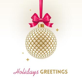 Świąteczna kartka z życzeniami - bombka bożonarodzeniowa wzorzysta złota z różową kokardką