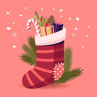 Świąteczna skarpeta z prezentami i słodyczami. tradycyjny prezent od świętego mikołaja, wystrój bożonarodzeniowy na kominek lub jodły