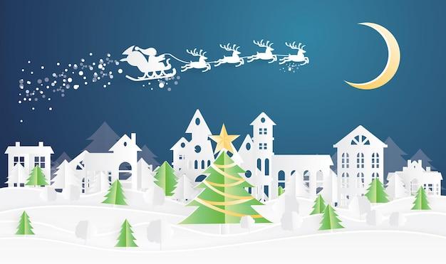 Świąteczna wioska i święty mikołaj w saniach w stylu wycinanym z papieru. zimowy krajobraz z księżycem.