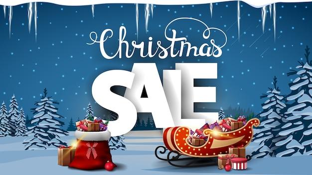 Świąteczna wyprzedaż, baner rabatowy z torbą świętego mikołaja, sanie świętego mikołaja z prezentami, białe litery wolumetryczne i zimowy krajobraz z ośnieżonymi sosnami