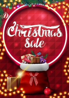 Świąteczna wyprzedaż, czerwony pionowy baner z girlandą, gałązki choinki, neonowe koło, piękny napis i worek świętego mikołaja z prezentami