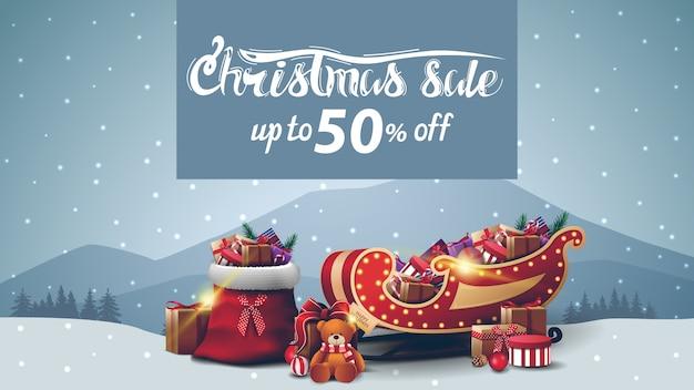 Świąteczna wyprzedaż, do 50% zniżki, banner rabatowy z szarym zimowym krajobrazem, torba świętego mikołaja, sanie świętego mikołaja z prezentami i prezentem z misiem