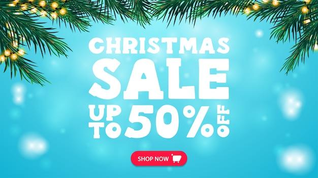 Świąteczna wyprzedaż, rabat do 50%, niebieski baner rabatowy z ramką z gałęzi choinki ozdobioną girlandą, guzikiem i dużą białą ofertą