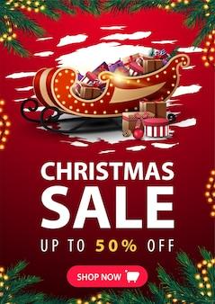 Świąteczna wyprzedaż, rabat do 50%, pionowy czerwony baner rabatowy w abstrakcyjnym kształcie reggad, ramka na girlandę, ramka z gałęzi choinki, guzik i sanie świętego mikołaja ze stosem prezentów