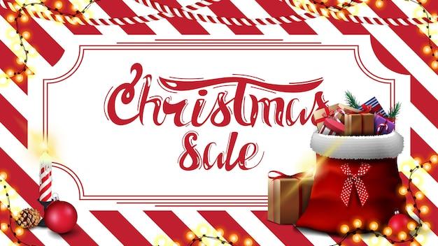 Świąteczna wyprzedaż, sztandar z rabatem z czerwono-białymi pasiastymi teksturami w tle i torba świętego mikołaja z prezentami