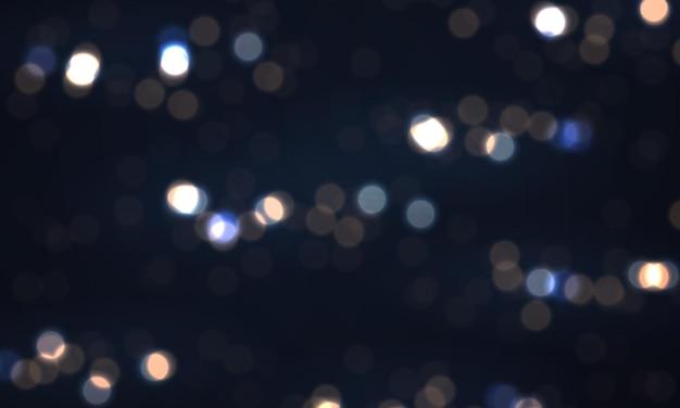 Świąteczne niebieskie świecące tło z kolorowymi światłami bokeh błyszczy z latającymi świecącymi cząsteczkami