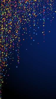 Świąteczne nowoczesne konfetti. gwiazdy uroczystości. tęczowe konfetti na ciemnym niebieskim tle. świeży świąteczny szablon nakładki. pionowe tło wektor.
