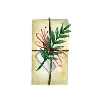 Świąteczne pudełko owinięte w papier i ozdobione gałązkami i wstążkami