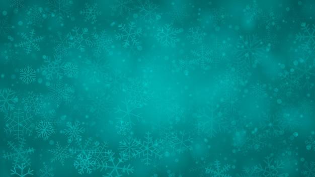 Świąteczne tło płatków śniegu o różnych kształtach, rozmiarach i przezroczystości w jasnoniebieskich kolorach