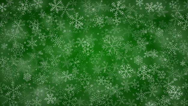 Świąteczne tło płatków śniegu o różnych kształtach, rozmiarach i przezroczystości w zielonych kolorach