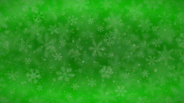 Świąteczne tło płatków śniegu o różnych kształtach, rozmiarach, rozmyciu i przezroczystości w zielonych kolorach