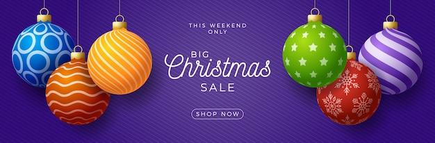 Świąteczny baner promocyjny sprzedaży poziomej. wakacyjna ilustracja z realistycznymi ozdobnymi kolorowymi bombkami na fioletowym tle.