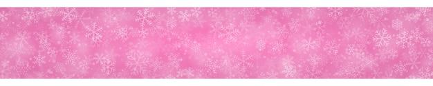Świąteczny sztandar płatków śniegu o różnych kształtach, rozmiarach i przezroczystości na różowym tle