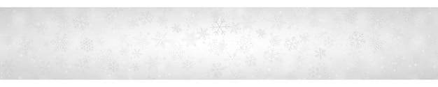 Świąteczny sztandar płatków śniegu o różnych kształtach, rozmiarach i przezroczystości na szarym tle