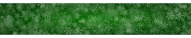 Świąteczny sztandar płatków śniegu o różnych kształtach, rozmiarach i przezroczystości na zielonym tle