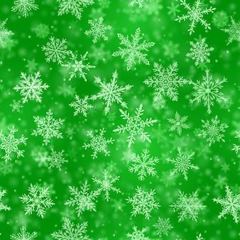 Świąteczny wzór złożonych niewyraźnych i wyraźnie spadających płatków śniegu w zielonych kolorach z efektem bokeh