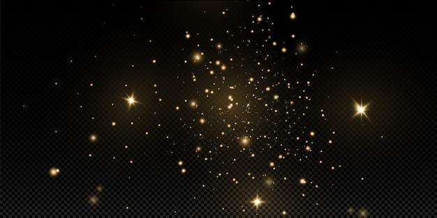 Świąteczny złoty pył, żółte iskry i złote gwiazdy lśnią specjalnym światłem. mieni się błyszczącymi cząstkami magicznego pyłu.
