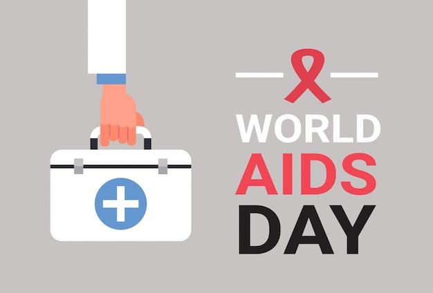 Światowy dzień aids świadomości czerwoną wstążką znak ręka trzymać zestaw pierwszej pomocy profilaktyka medyczna