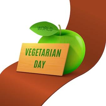 Światowy dzień wegetarianizmu zielone realistyczne jabłko na czerwonej wstążce