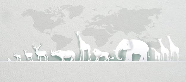 Światowy dzień zwierząt z jeleniem, słoniem, lwem, żyrafą, królikiem, nosorożcem na mapie świata w stylu papierowym, wycinanym z papieru i origami. ilustracja światowy dzień dzikiej przyrody zwierząt w tekstury papieru.