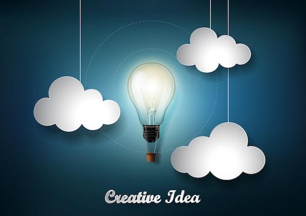 Świecąca żarówka jest jednym z wielu chmur na ciemnoniebieskim tle w stylu cięcia papieru origami, reprezentacja koncepcji kreatywnego pomysłu na biznes