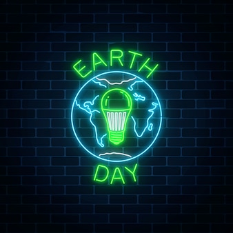 Świecące neon światowy dzień ziemi z symbolem świata i zielone żarówki led w środku.