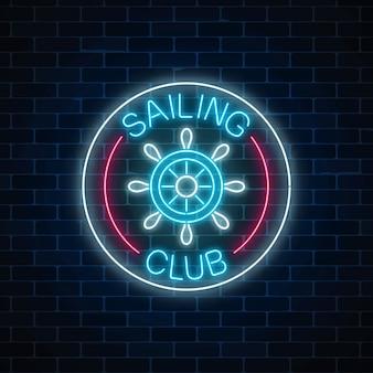 Świecące neon znak klubu żeglarskiego z kierownicą w ramkach koło na tle ciemnego muru.