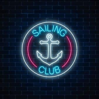 Świecące neon znak klubu żeglarskiego z symbolem kotwicy w ramkach koło na tle ciemnego muru.