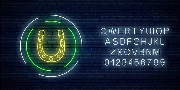 Świecący neon z podkowy w ramie koło z alfabetem na tle ciemnego ceglanego muru. emblemat podkowy w neonowym stylu na szczęście. ilustracja wektorowa.