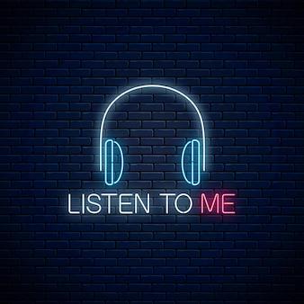 Świecący neon ze słuchawkami i posłuchaj mnie hasłem na tle ciemnego ceglanego muru. wezwanie do słuchania symbol z wiwatującym napisem. ilustracja wektorowa.
