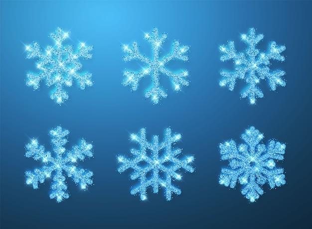 Świecący niebieski brokat świecący płatki śniegu na niebieskim tle. dekoracja świąteczna i noworoczna.