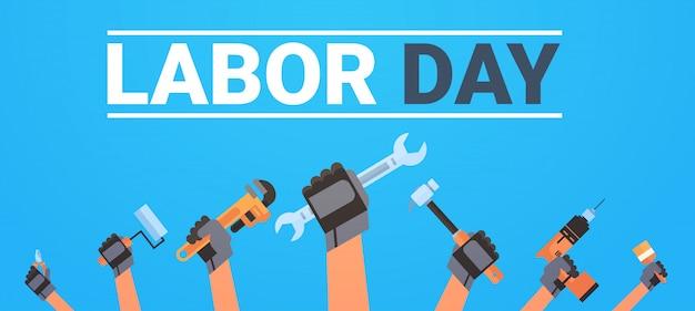 Święto pracy z rękami trzymając różnych instrumentów pracowników wakacje
