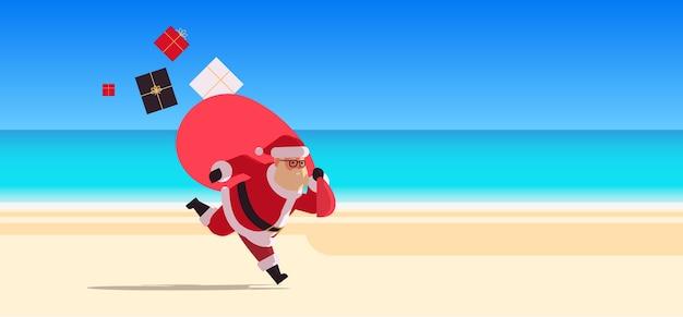Święty mikołaj biegnie z dużym workiem pełnym prezentów szczęśliwego nowego roku boże narodzenie wakacje wakacje koncepcja uroczystości tropikalna plaża pejzaż morski tło pełnej długości płaska
