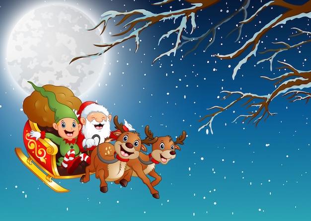 Święty mikołaj i elf jadący saniami latającymi w zimową noc