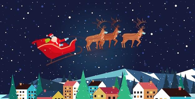 Święty mikołaj latający w saniach z reniferami na nocnym niebie nad domami wiejskimi szczęśliwego nowego roku wesołych świąt transparent ferie zimowe koncepcja powitanie pozioma ilustracja