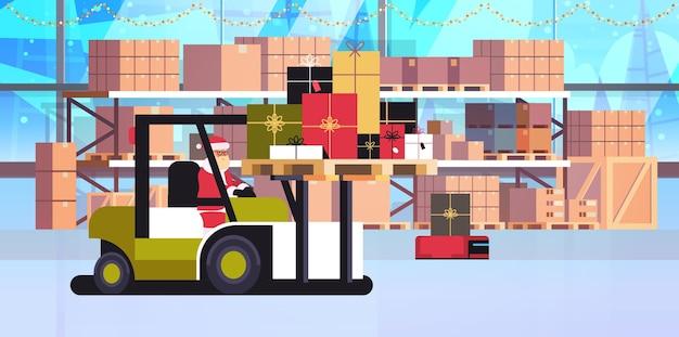 Święty mikołaj na wózku widłowym ładowanie kolorowe prezentowe pudełka koncepcja dostawy i wysyłki wesołych świąt szczęśliwego nowego roku ferie zimowe magazyn uroczystości
