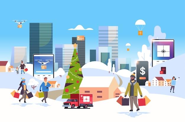 Święty mikołaj niosący pudełka z prezentami ludzie z torbami na zakupy spacerujący na zewnątrz przygotowujący się do świąt bożego narodzenia nowy rok wakacje mężczyźni kobiety korzystający z aplikacji mobilnej online zimowy pejzaż miejski