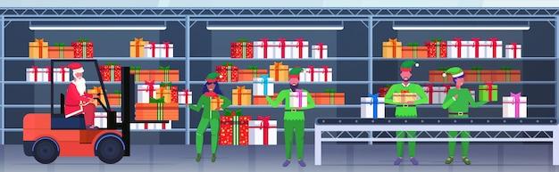 Święty mikołaj prowadzący wózek widłowy elfy ładujące kolorowe pudełka z prezentami na przenośnik taśmowy wesołych świąt szczęśliwego nowego roku