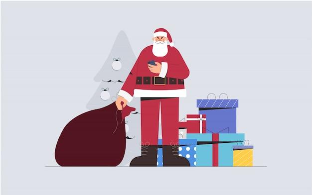 Święty mikołaj trzyma torbę prezentów i telefon