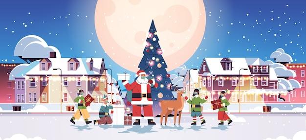 Święty mikołaj z mieszanką rasy elfy w maskach przygotowuje prezenty szczęśliwego nowego roku wesołych świąt bożego narodzenia uroczystość koncepcja pejzaż miejski pełna długość pozioma wektorowa ilustracja
