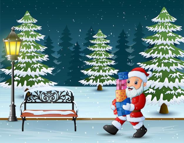 Święty mikołaj z pudełkami prezenta odprowadzenie przez winter park