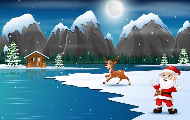 Święty mikołaj z reniferem przy zima krajobrazem